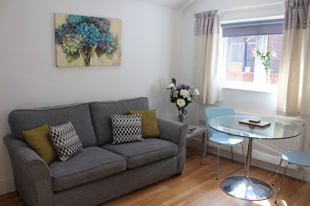 Open plan living/dining room with sofa bed.